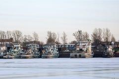 Flodbogserbåtar i vintern på pir royaltyfri bild