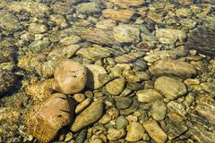 Flodbotten, stenar i floden, stenig nordlig flod, arkivfoto