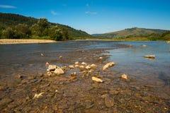 Floden flödar till och med berg Carpathians Arkivbilder