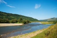 Floden flödar till och med berg Carpathians Royaltyfria Foton