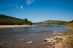 Floden flödar till och med berg Carpathians Royaltyfri Bild