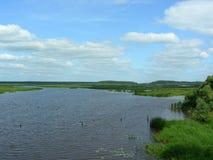 Floden flödar till och med breda flodmynningarna som ut spiller Arkivfoto