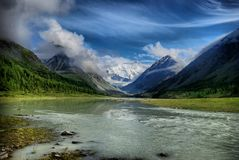 Floden i utlöparen av Sikhoten-Alin En taigaflod Floden med skogsbevuxna kuster och den blåa molnfria himlen Far East arkivfoto