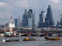 Floden rusar på thamesen med staden av london byggnader Fotografering för Bildbyråer