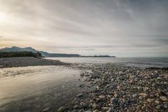 Floden sammanfogar havet på ett Pebble Beach i Korsika arkivfoto