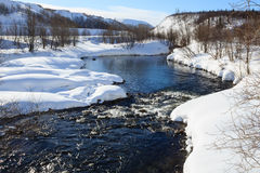 Floden som flödar över stenar, snöar och träd i polar stad Arkivfoto