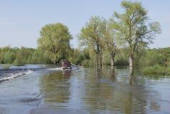 Floder översvämmade det vägtraktoren bär bilar. Royaltyfri Bild