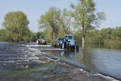 Floder översvämmade det vägtraktoren bär bilar. Royaltyfria Bilder