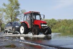 Floder översvämmade det vägtraktoren bär bilar. Fotografering för Bildbyråer