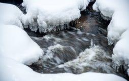 flodflöda och snö på stenar royaltyfria bilder
