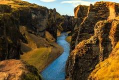 Flodflöde till och med den stora kanjonen av Fjadrargljufur, Island Arkivfoto