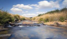 Flodlandskap i drakensberg med moln och berget Royaltyfri Foto