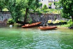 Flodlandskap med träfartyg som ankras på banken arkivbild