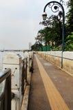 Flodsidan går och den elektriska stolpen i skymning Arkivfoto