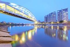 Flodstrandbyggnader och den berömda HuanDong regnbågebron över den Keelung floden på skymning i Taipei Taiwan, Asien Arkivfoton