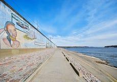 Flodstrandpromenad och väggmålning på en vägg vid Mississippi River arkivbilder