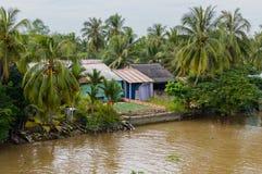 Flodstrandstyltahus i den Mekong deltan arkivfoton