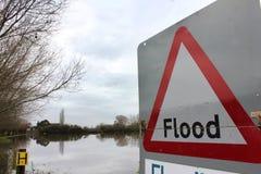 Flodvarningstecken vid översvämmat land Royaltyfri Bild