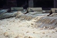 Flodvatten som snabbt flödar över en överflödfördämning Arkivfoton