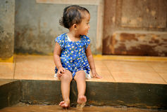 Flood. Little Indonesian girl playing in a water during a flood royalty free stock image