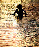 After the Flood. A silhouette photo of a child enjoying the  remnants of a flood Stock Images