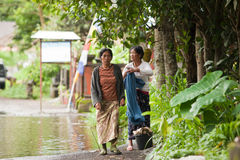 Flood. LAKE BATUR, BALI - JANUARY 21. Women walking through flooded street after downpour on Lake Batur on January 21, 2012 in Bali, Indonesia. Weather patterns Royalty Free Stock Images