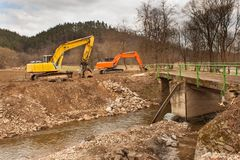 Flood adjustments river. Work on the riverbed. Excavator on the work to strengthen the shoreline of the river. Royalty Free Stock Images