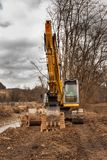 Flood adjustments river. Work on the riverbed. Excavator on the work to strengthen the shoreline of the river. Royalty Free Stock Photo