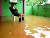 Flood caused by typhoon Mario (international name Fung Wong) in the Philippines on September 19, 2014. A Resident of Cainta, Rizal sits in his flooded garage stock photography