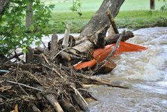 Flood debris. A collection of debris and trash being pushed against a downed tree by rushing waters Stock Photos