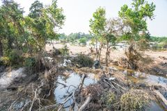 Flood debris. Many uprooted trees and pile of debris on dangerous part of landslip river/stream section after flooding by heavy rains of Harvey hurricane storm Royalty Free Stock Photos