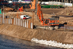 Flood defences. Industrial contractor completing public works and strengthening river bank flood defences with verticle steel piles Royalty Free Stock Images