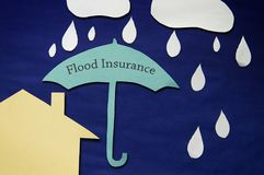 Flood insurance concept. Paper umbrella in a rain storm, over a house -- flood insurance concept stock photo