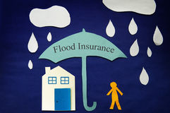 Flood insurance coverage. Paper cutout man under a flood insurance umbrella Stock Images