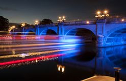 Flood lit bridge at night with long exposure light strikes stock photography