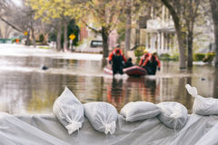 Flood Protection Sandbags. With flooded homes in the background Montage royalty free stock photography