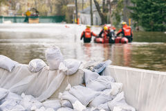 Flood Protection Sandbags. With flooded homes in the background Montage Stock Photos