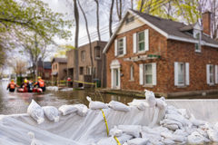 Flood Protection Sandbags. With flooded homes in the background Montage royalty free stock image