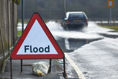 Flood Sign. Motorist driving through flood waters with warning sign in foreground stock photo