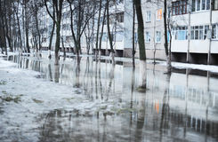 Flood on the street. Spring high water in the residential area of the city Stock Photos