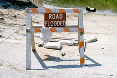Flood Warning. A flood sign stands before a flooded road Royalty Free Stock Photos