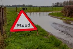 Flood. A flood warning road sign beside a flooded road Stock Photography