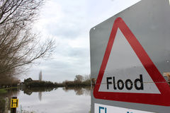 Flood Sign Warning by Flood. UK flood sign overlooking flooded land in rural area royalty free stock image