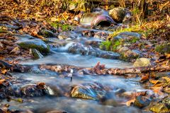 Flood water gushes through an intersting pipe and downed branches surrounded by colorful fall foliage. Ironic beauty concept stock images