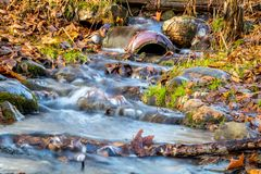 Flood water gushes through an intersting pipe and downed branches surrounded by colorful fall foliage. Ironic beauty concept stock photo