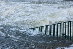 Flood water raging away. Picture depicting flood water covering a city street royalty free stock image