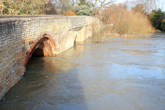Flood water under a stone bridge. Swollen river runs very fast under the arches of a stone bridge. This was taken in the heavy rainy period in the United Stock Photography