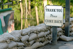Flood Waters. An ironic sign stands before flood waters held back by sandbags royalty free stock photography