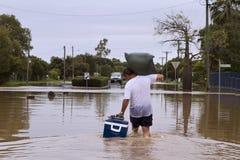 Flood waters. Man walking through brown muddy flood waters carrying out his belongings Stock Photo