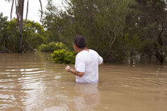 Flood waters. Man walking through waist high flood waters to get to his home Stock Images